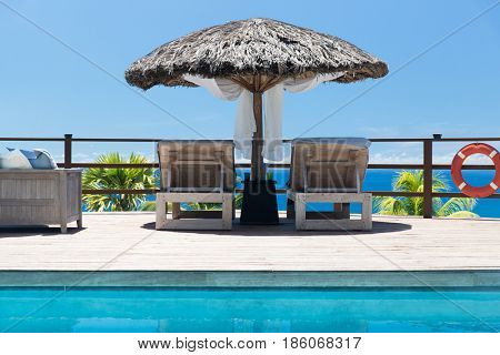travel, tourism, vacation and summer holidays concept - palapa and sunbeds at seaside swimming pool