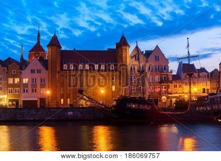 Night in Gdansk - old town waterfront with sailing ship illuminated in night, Gdansk, Poland