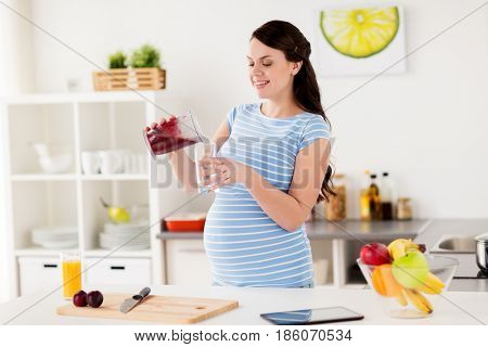 healthy eating, cooking, pregnancy and people concept - pregnant woman with blender cup pouring fruit smoothie drink into glass at home kitchen