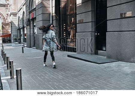 Carefree city style. Full length rear view of young woman looking over her shoulder while walking down the street
