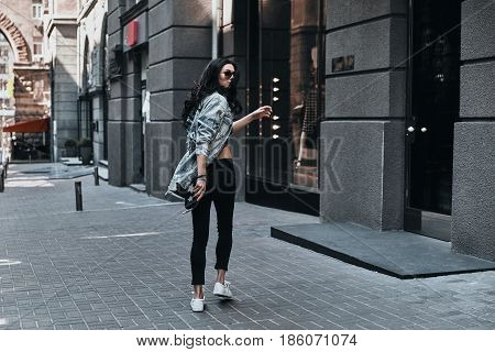 Looking amazing. Full length rear view of young woman looking over her shoulder while walking down the street