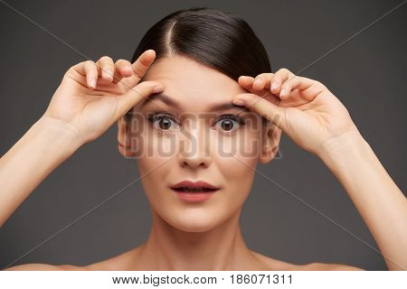 Beautiful young woman rising her eyebrows with hands: facial expression causing wrinkles