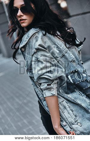 Like my style? Attractive young woman looking over her shoulder while walking down the street