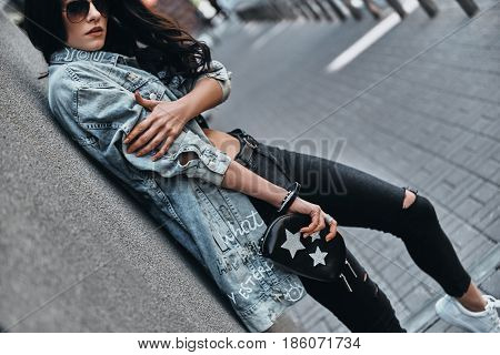 Trendy look. Beautiful young woman in denim jacket looking at camera while leaning on the building outdoors