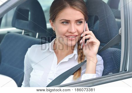 Portrait of a businesswoman talking on mobile phone in the car. Business woman on the phone at work