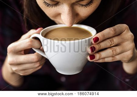 White young woman holding a cup of coffee in her hands and drinking it while coffee break.