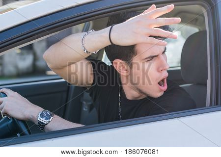 Handsome Angry Young Man Driving a Car and Yelling to someone in front of him