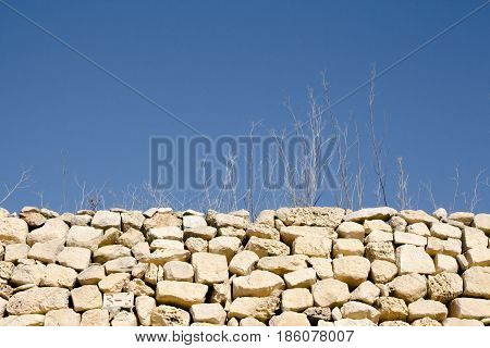 Abstract shot of sticks and grass in dry weather and rubble wall. Isolated typical elements of maltese countryside rural areas. Horizontal landscape orientation.
