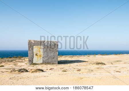 Illegally constructed concrete shelter on limestone cliffs in Gozo Malta close to wied il-mielah. Barren landscape with the sea and blue sky.