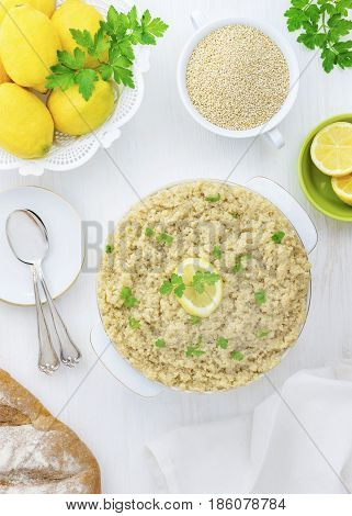 Cooked Quinoa with uncooked by the side in a vertical bright and airy over head image with lemons and herbs,on a white wooden backgound .