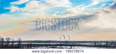 Smoking chimneys of a power station on the horizon