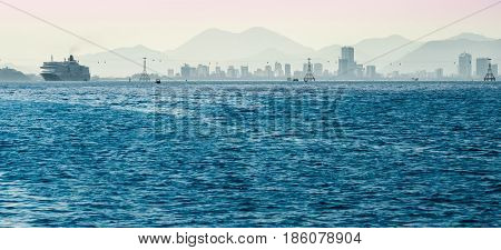 A large cruise ship and the city on the horizon
