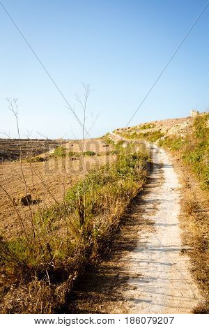 Dirt path winding through fields in the countryside around Wied il-Mielah. Gozo Malta Zebbug.