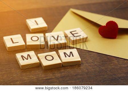 I love mom wording with red heart sign and envelope on old wooden background Mother's day concept.