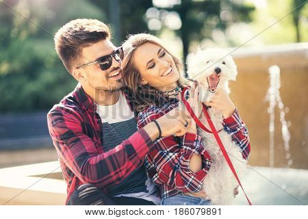 Young couple with puppy. Portrait of attractive happy smiling young woman and man holding cute little dog summer park outdoor.