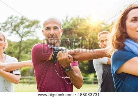 Mature man stretching at park while listening to music with group of people. Senior multiethnic man working out with his freinds. Healthy man with class doing stretching exercises.