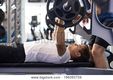 Determined young man lifting barbell. Latin man doing barbell bench press in gym with personal trainer. Man in gym exercising with barbell.