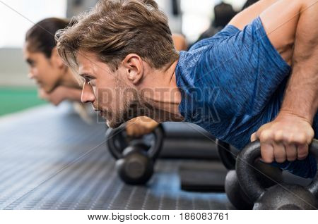 Young man doing push up using kettlebells. Strong guy using kettlebells at gym during exercise. Determinated man doing push ups with kettle bell at the fitness centre.