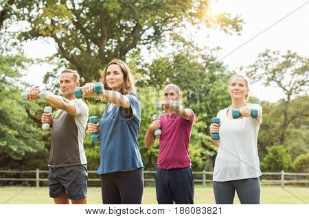 Group of mature people exercise using dumbbell at park. Team of four mature people using weights outdoor. Smiling men and mid women using dumbbell for workout in park.