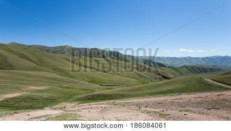 Photo of Kochkor's green valley landscape in Kyrgyzstan