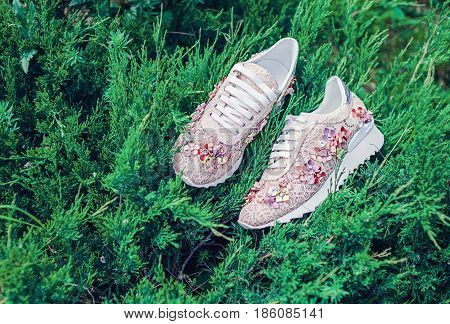 Beige fashionable sneakers with flowers and rhinestones on a background of greenery. Italian brand shoes.