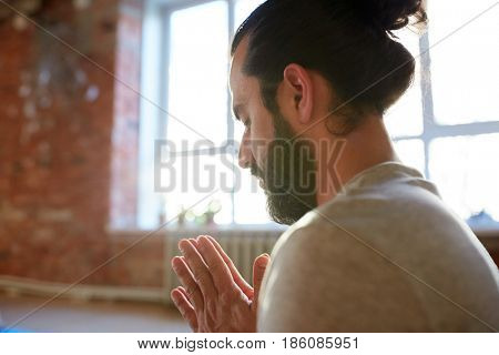 religion, faith and people concept - close up of woman meditating or praying at yoga studio
