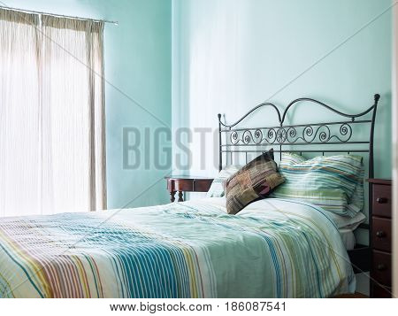 Bright and airy bedroom with rustic furniture and green / turquoise paint and soft furnishings from a bed and breakfast.