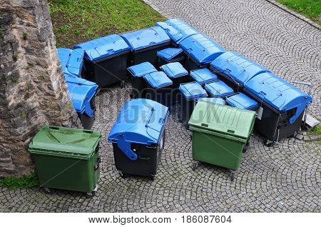 Many blue and green plastic containers for separate garbage.