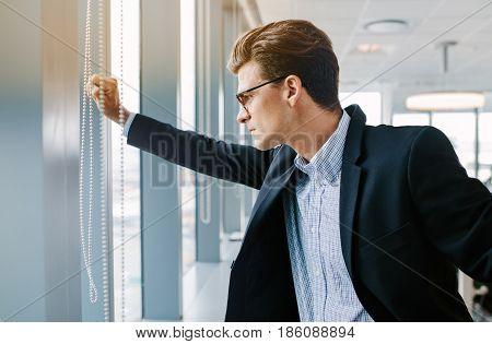 Side view shot of mature businessman standing in office. Caucasian male executive standing by window and looking outside.