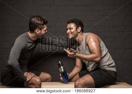 Handsome Male Athletes Resting And Conversing At Gym Locker Room