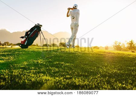 Low angle shot of professional golfer taking shot while standing on field. Full length of golf player swinging golf club on sunny day.