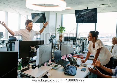 Young man showing excitement after closing a deal standing at his desk with arms wide open and looking at colleagues. Business man looking happy after the successful deal.