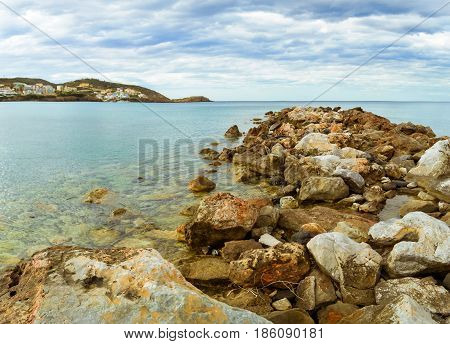 Breakwater of huge rocks going out to sea. Marine spit on beach Livadi in sea bay of resort village Bali in may. Views of mountain shore washed by waves where sunbathing tourists. Crete Greece