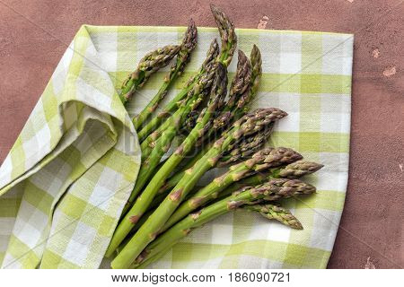 Fresh asparagus on concrete background, top view.
