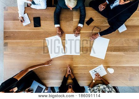 Group Of Businesspeople Placing Blank Placards On Table