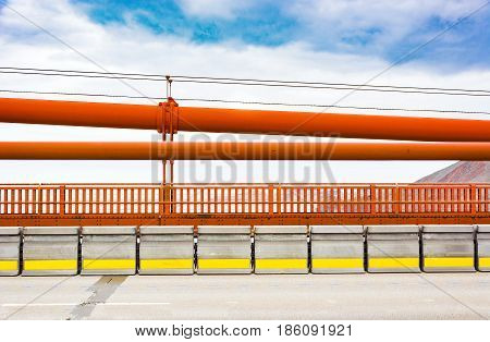 golden gate bridge railings with the iron suspension cables above
