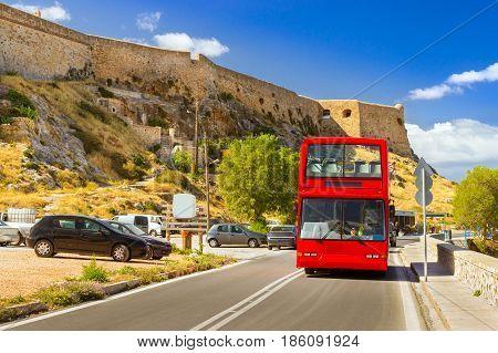 Red open double-Decker sightseeing bus traveling on highway along promenade Emmanouil Kefalogianni. Venetian fortress Fortezza Castle hill Paleokastro in resort Rethymno Crete Greece