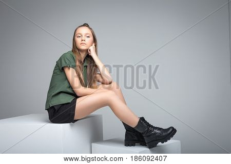Young cute slender model sitting on white cube. woman dressed in green T-shirt, black shorts and large army boots
