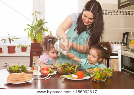 Family preparing meal together. Happy mother and her cute twin daughters having fun cooking vegetable salad.