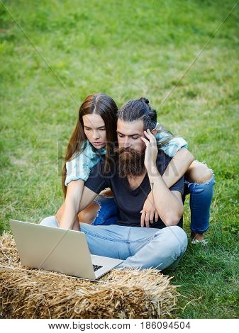 Couple In Love Using Laptop On Nature