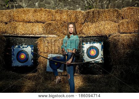 Archer Holding Bow And Arrow At Archery Targets