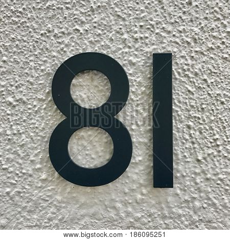 Number 81 painted black metal house address sign screwed into painted white wall textured background