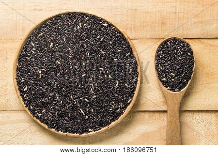 Thai black jasmine rice or Rice berry in bowl and spoon on wooden table.