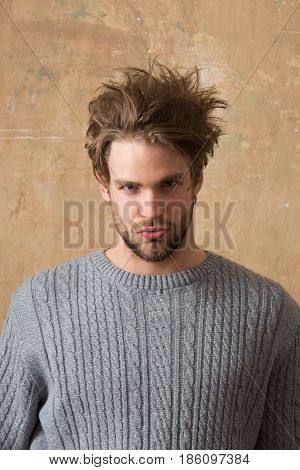 man. Handsome bearded man with beard or sexy caucasian macho on beige wall background. Stylish blond hair haircut and young unshaven face skin. Male beauty and hairdressing.