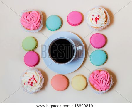 White coffee cup with colorful macaroons and cupcakes on beige background