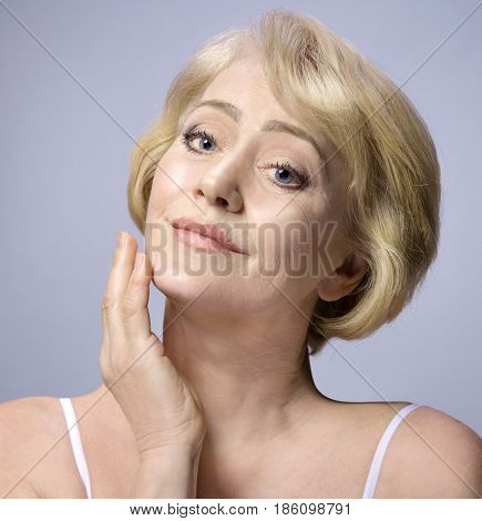 Beautiful Matured Woman Touching her Face with hand. cheerful caucasian smiling blond. Studio shot. Looking off camera. Facecare. Grey background. 50 . Skin care concept