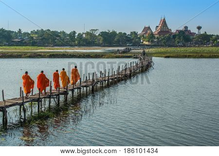 MAHASARAKHAM THAILAND - DECEMBER 20 2015: Buddist monks getting back temple after seeking alms. This is usual every day duty of Buddhist monks.