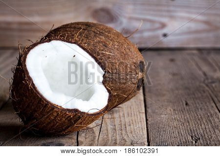Ripe half cut coconut on a wooden background. Ripe half cut coconut on a wooden background. Coconut cream and oil. a