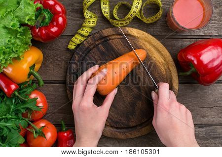 Female hands cutting carrot at table, top view. On the table leaves of lettuce, pepper, a glass of tomato juice, a wooden board and a knife