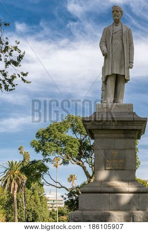 Auckland New Zealand - March 5 2017: White stone statue of Sir George Grey on pedestal in Albert Park under blue cloudy sky with green trees in back.
